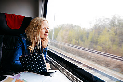 Portrait of smiling blond woman with notebook travelling by train looking out of window - p300m2103561 von Epiximages