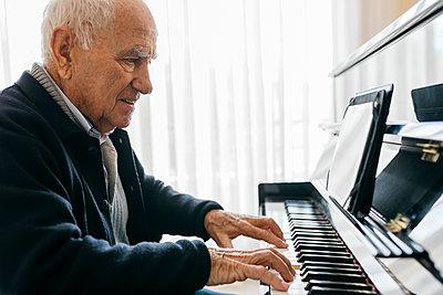 Senior man sitting in wheelchair playing piano at home - p300m2160168 von Josep Rovirosa