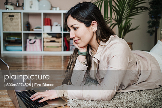 Female professional lying on rug while using laptop at home - p300m2274528 by Eva Blanco