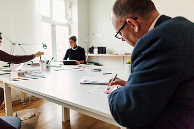 Rear view of businessman signing contract while businesswomen working in background - p1185m1016012f by Astrakan