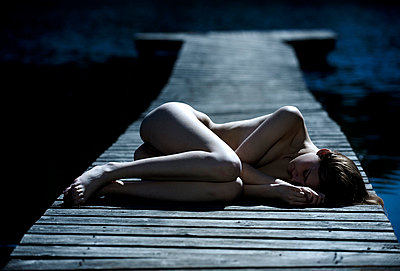 Woman lying naked on a boardwalk - p5560158 by Wehner