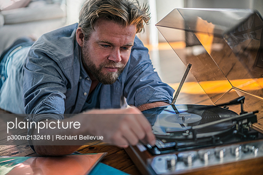 Man lying on the floor at home with a record player - p300m2132418 by Richárd Bellevue