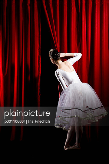A ballet dancer peeking through a stage curtain, rear view
