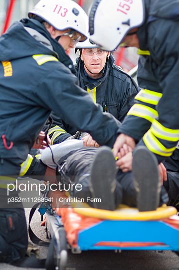 Sweden, Sodermanland, Firefighters bending over man lying on stretcher