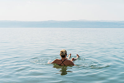 Woman floating, swimming in Dead Sea, Jordan - p1023m2067705 by Anna Wiewiora