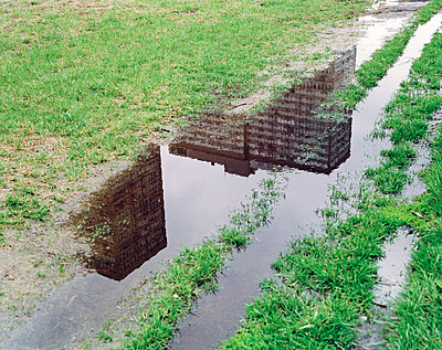 Reflection of Building in Puddle - p1614m2185778 by James Godman