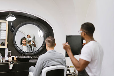 Barber showing man his haircut in mirror at barber shop - p300m2113955 by Hernandez and Sorokina