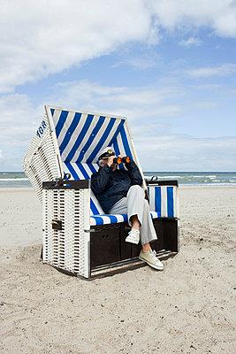 A senior man sitting in a hooded beach chair looking through binoculars - p3019720f by Paul Hudson
