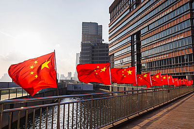 Row of Chinese flags on Huangpu river promenade, Shanghai, China - p429m2074661 by Henglein and Steets