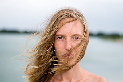 Young woman with hair blowing in wind - p552m1161307 by Leander Hopf