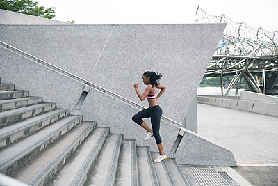 Mixed Race woman running up urban staircase - p555m1301934 by Hello Lovely