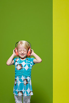 Little girl with eyes closed wearing protective headphones - p62314447f by Matthieu Spohn