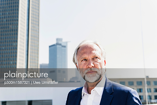 Portrait of serious mature businessman in the city looking around - p300m1587321 von Uwe Umstätter