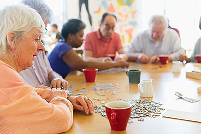 Senior woman assembling jigsaw puzzle with friends at table in community center - p1023m2010092 by Tom Merton
