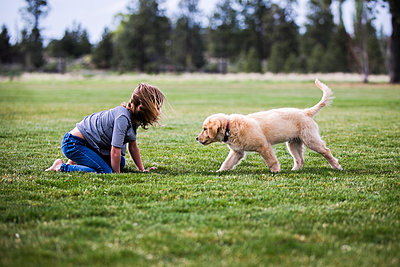 Side view of girl playing with dog on field - p1166m1226057 by Cavan Images