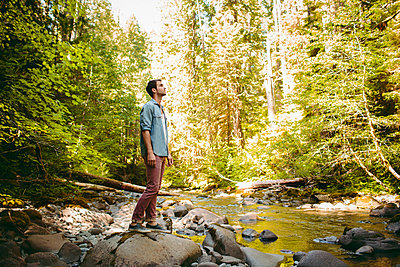 Full length of man standing on rock by river in forest - p1166m1423034 by Cavan Images