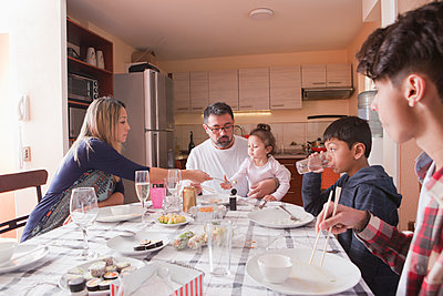 Family eating sushi at dining table - p1427m2085092 by REB Images