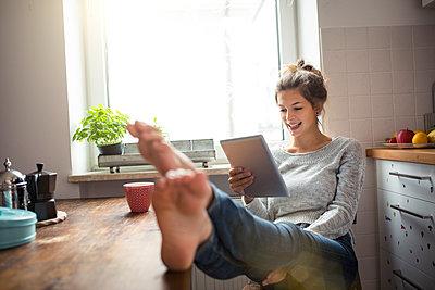 Woman sitting at table in kitchen using tablet - p300m1568364 von Philipp Nemenz