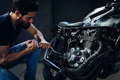 Young male motorcyclist repairing vintage motorcycle in garage - p429m2202353 by Sofie Delauw