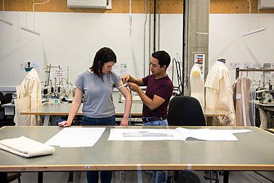 Fashion students, man measuring woman's arm - p429m2252729 by G. Mazzarini