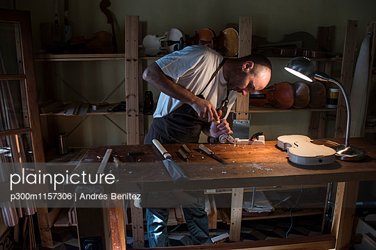 Luthier using a chisel on a violin scroll during the manufacture of a violin in his workshop - p300m1157306 by Andrés Benitez