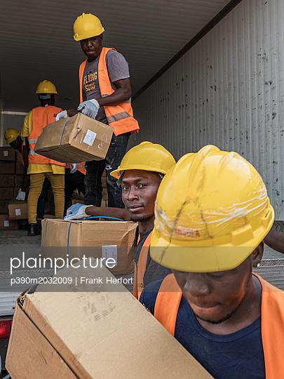 Lagerarbeiter beladen einen Kühltransporter mit gefrorenem Fisch - p390m2032009 von Frank Herfort