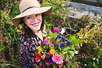 happy woman in an urban garden - p1166m2136991 by Cavan Images