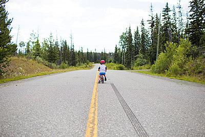 rear view of young boy biking on balance bike. - p1166m2147314 by Cavan Images