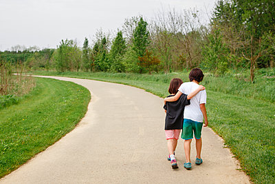 A small boy and girl walk arm in arm down curved path in a park - p1166m2261269 by Cavan Images