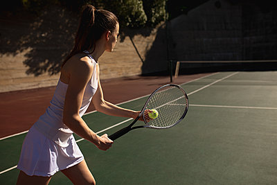 Woman playing tennis on a sunny day - p1315m2131515 by Wavebreak