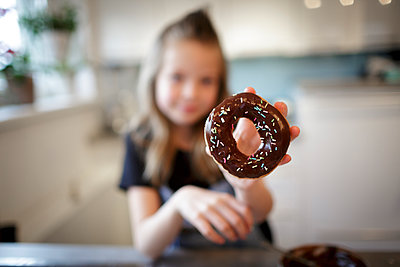 pretty girl bakes donuts with chocolate and sprinkles in modern kitchen, lower austria - p300m2180233 von Epiximages