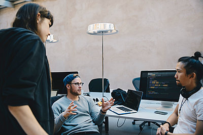 Computer programmer gesturing while discussing plan with colleagues in creative office - p426m1493961 by Maskot