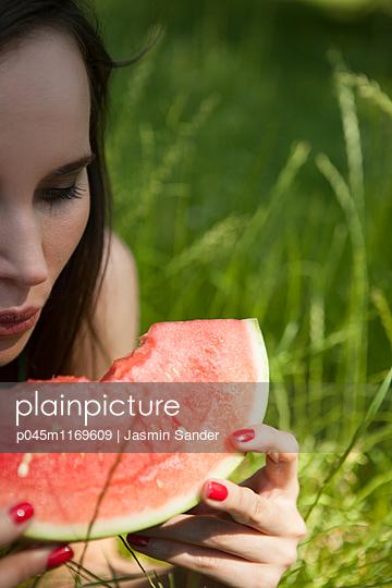 Im Gras eine Wassermelone vernaschen - p045m1169609 von Jasmin Sander