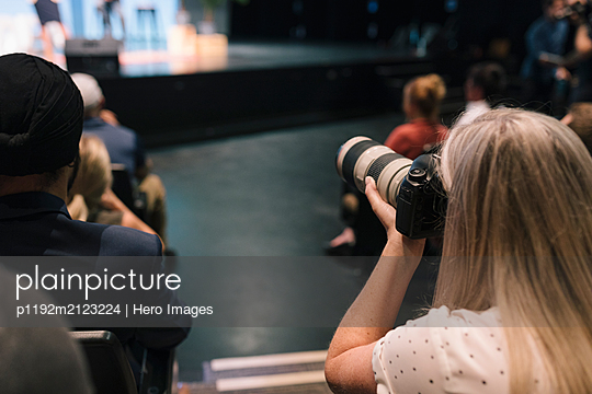Female photographer with digital camera at presentation - p1192m2123224 by Hero Images