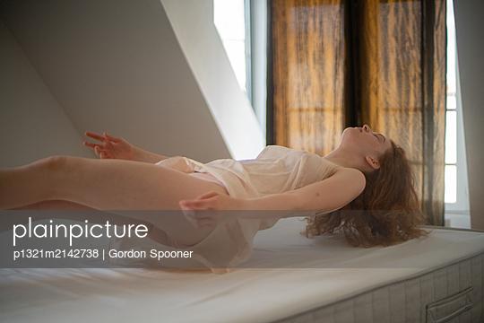 Schwebende Frau auf dem Bett - p1321m2142738 von Gordon Spooner