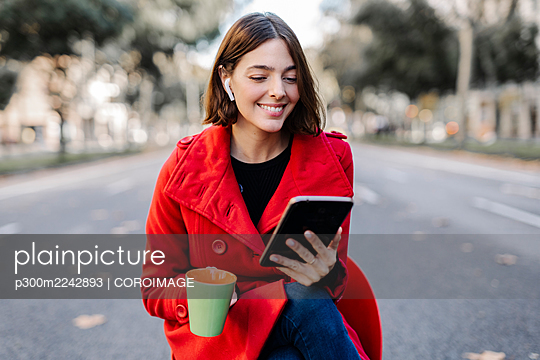 Smiling fashionable young woman with coffee cup using digital tablet on street - p300m2242893 by COROIMAGE