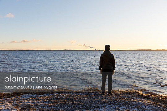Mature woman standing next to Lake Glan at sunset in Sweden - p352m2120010 by Åke Nyqvist