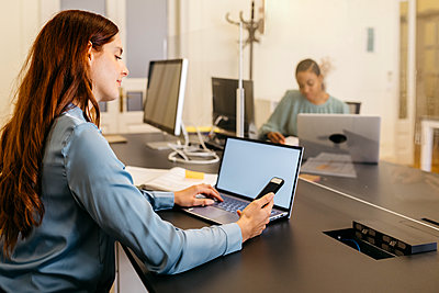 Businesswoman using smart phone and laptop while sitting at office desk - p300m2226149 by Josep Rovirosa