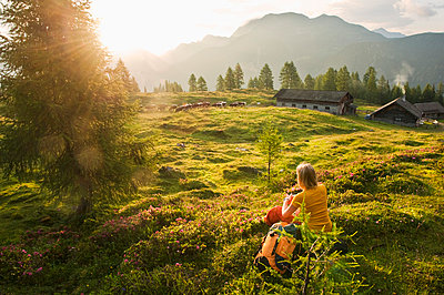 Young woman sitting in alpine meadow and watching landscape - p300m659934f by Hans Huber