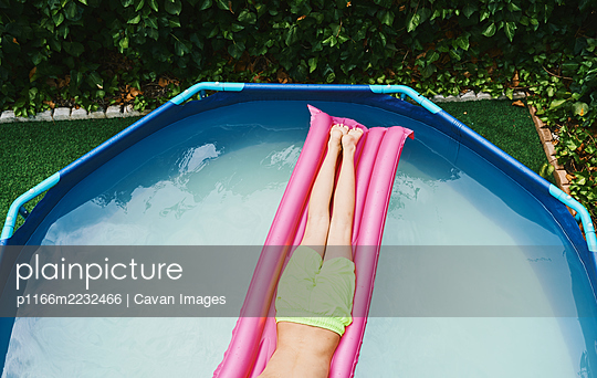 Cenital view of part of a boy lying on a pink float resting in a pool. - p1166m2232466 by Cavan Images