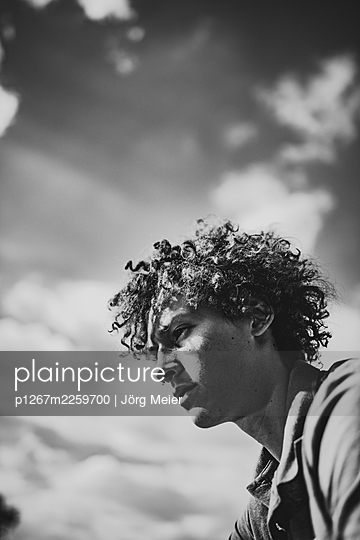 Young man with curly hair, portrait - p1267m2259700 by Jörg Meier