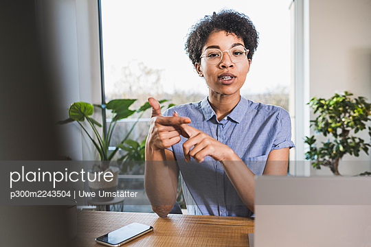 Woman sitting in front of computer, having video conference - p300m2243504 by Uwe Umstätter