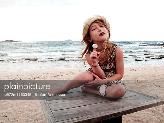 Mädchen posiert kokett am Strand - p972m1160348 von Stefan Andersson