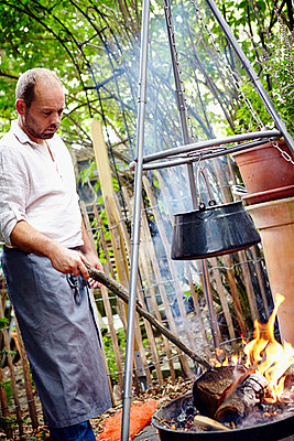 Man Tending To Bonfire - p1026m857181f by Dario Secen
