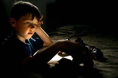 Young boy in blue shirt playing with cars on a bed in bedroom - p1166m2268984 by Cavan Images