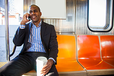 Black businessman talking on cell phone and riding commuter train - p1427m2271537 by Peter Dressel