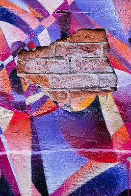 Rote Backsteine durchbrechen ein Graffiti - p177m1214592 von Kirsten Nijhof