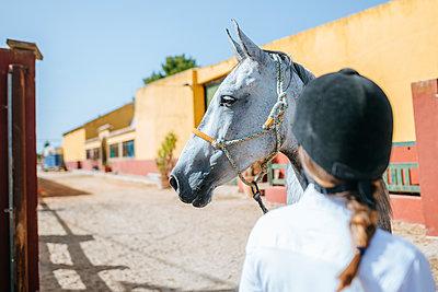 Portrait of horse with back view of woman wearing riding helmet - p300m1494788 by Kiko Jimenez