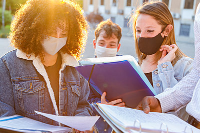 Male and female students wearing protective mask while discussing notes in university campus - p300m2225894 by Ignacio Ferrándiz Roig