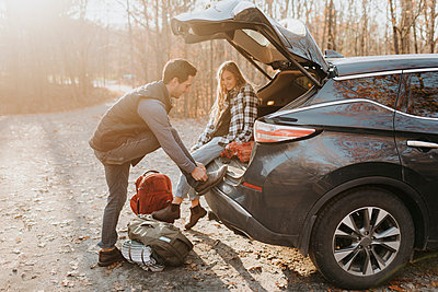 Young couple leaving car before hiking in autumn forest - p300m2241673 by Sara Monika